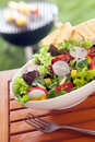 Veggie healthy fresh vegetarian salad on a picnic table leafy green mixed wooden with slices of roasted flatbread and summer Royalty Free Stock Photography