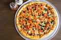 Veggie pizza with olives and cherry tomatoes on the table Stock Photos
