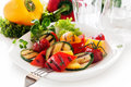 Veggy succulent grilled vegetables with assorted sweet peppers baby marrow and tomato garnished with herbs served in a dish with Stock Photo