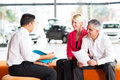 Vehicle salesman contract explaining to senior couple before buying a car Stock Image