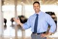 Vehicle salesman presenting friendly new cars at showroom Stock Image