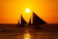 Veleros en la puesta del sol en un mar tropical foto de la silueta Fotos de archivo