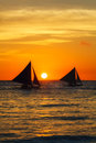 Veleros en la puesta del sol en un mar tropical foto de la silueta Fotografía de archivo