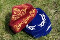 Velvet hats red and blue embroidered festive headwear atop green grass Stock Images