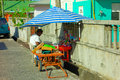 A vendor catering to schoolchildren on bequia an enterprising woman selling junkfood waiting for school be out Royalty Free Stock Image