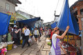 Vendors are keeping their stalls away from the coming train at maeklong railway market this is a common daily activity and scene Stock Photos