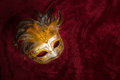 Venetian carnival mask on a draped red velvet theater curtain Royalty Free Stock Photo