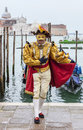 Venetian costume venice italy march unidentified man disguised in a beautiful medieval posing in front of the gondola s pier near Stock Image