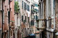 Venetian houses one of the many small canals surrounded by historic with faded flair and signs of decay Royalty Free Stock Photography
