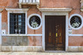 Venetian old house facade with wooden door and metal bars on windows Stock Photo