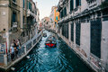 Venetian street canal with various boats on it, tourists walk alongside. Royalty Free Stock Photo