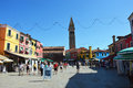 Venice Burano square with tourists, leaning campanile tower bells and typical colorful houses on the bottom, Venice Royalty Free Stock Photo