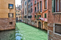 Venice canal with typical water doors arched leading to the green and laundry hanging drying against the red bricks of the Royalty Free Stock Photo