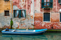 Venice cityscape, boat on narrow water canal near colorful wall with windows Royalty Free Stock Photo