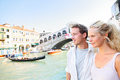 Venice couple by rialto bridge on grand canal travel together young happy holidays or honeymoon having cute romantic Stock Images
