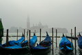 Venice gondolas and the fog bob as sentinels in as church in background watches over Royalty Free Stock Photo