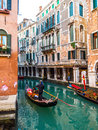 Venice gondolier driving gondola on water canal Stock Photos