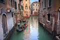 Venice image of gondolier in one of many narrow canals in Stock Photo
