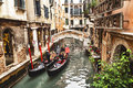 Venice, Italy – December 21, 2015: Tourists taking photo with gondolier in venetian canal in gondola. Venice. Italy. Royalty Free Stock Photo