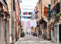 Venice italy december typical old venetian street people walking clothes hanging to dry and s flag with the winged lion symbol Stock Image