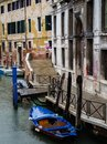 Venice italy may view of a side canal and old buildi buildings in the centre lady with umbrella crosses the bridge in the rain Royalty Free Stock Photo