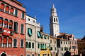 Venice italy palazzo schiavoni pink at left and a row of classic venetian houses with a towering church steeple near the grand Royalty Free Stock Images