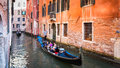 Venice tourists enjoy a gondola ride with sailing on typical canal bordered by old medieval buildings in italy Stock Photos