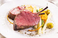 Venison carree with vegetables as closeup on a white plate Royalty Free Stock Photo