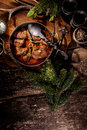 Venison goulash stew in pot with serving spoon high angle view of surrounded by evergreen sprigs and spices on rustic wooden Royalty Free Stock Photo