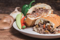 Venison stuffed french bread loaf on a white plate in rustic set Royalty Free Stock Photo