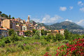 Ventimiglia and overgrown riverbed with trees shrubs grass old town of under blue sky in italy Royalty Free Stock Images