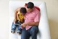 över huvudet sikt av fadern and son on sofa using digital tablet Royaltyfri Fotografi