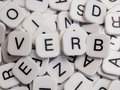Verb letters pile letter tiles Stock Photo