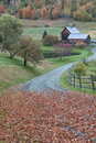 Vermont farm in autumn leaf covered road winds its way to Stock Photo