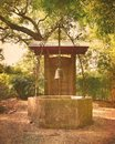 Old water well with ornate iron scrollwork & bell Royalty Free Stock Photo