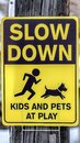 Vertical frame Black and yellow Slow Down Kids And Pets At Play sign against gray wooden pole Royalty Free Stock Photo