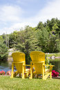 Vertical pair of yellow muskoka chairs at lake Royalty Free Stock Photo