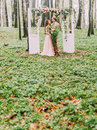 The vertical photo of the newlyweds dressed in vintage clothes and standing under the arch in the form of the white Royalty Free Stock Photo
