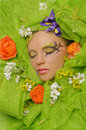 Vertical portrait of beautiful woman in flowers on green background Royalty Free Stock Image