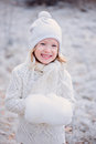 Vertical portrait of cute happy child girl in white outfit on the walk in winter snowy forest blonde Stock Photo
