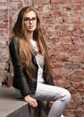 Vertical portrait of a stylish young woman. White jeans and black leather jacket Royalty Free Stock Photo