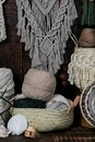 Vertical shot of baskets full of multicolored knitting wool balls and macrame hanging on the wall Royalty Free Stock Photo