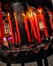 Vertical shot of burning red candles inside a church on a blurred background Royalty Free Stock Photo