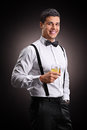 Vertical shot of a cheerful man drinking bourbon on black background Stock Image