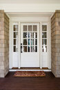 Vertical shot of an closed wooden front door a from the exterior upscale home with windows Royalty Free Stock Images