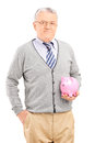 Vertical shot of a mature man holding a piggybank isolated on white background Stock Photos