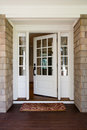 Vertical shot of an open wooden front door from the exterior upscale home with windows Stock Image