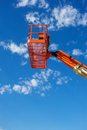 Vertical shot of an orange hydraulic construction lift utility used in the industry against a blue sky with white clouds Stock Photos