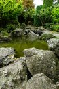 Vertical shot of stones around the pond in the fall in a Japanese garden Royalty Free Stock Photo