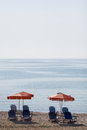 Vertical summer theme shot with chairs under umbrellas Royalty Free Stock Photography
